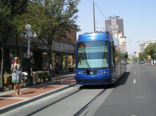 Tucson's new Sun Link streetcar passes sidewalk cafe during opening day festivities. Photo: Ed Havens.