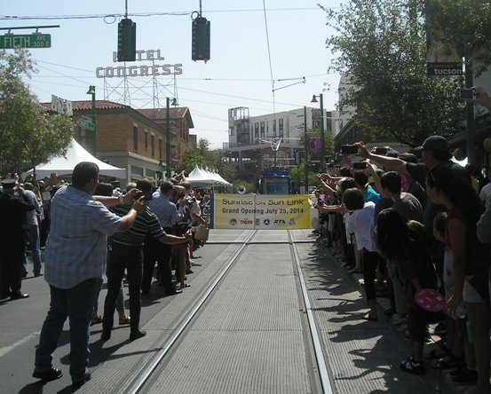 Jubilant crowd lines track for photo-op moment as Tucson's first modern streetcar approaches inauguration banner on opening day. Photo: Ed Havens.